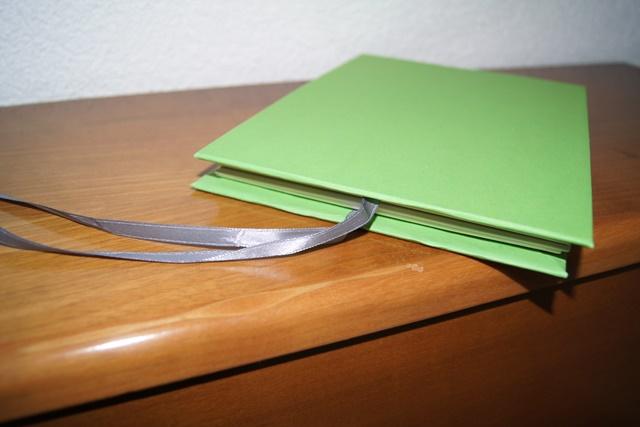 Die Seiten werden mit dem Einband verleimt, wobei das Satinband eingeschlossen wird.